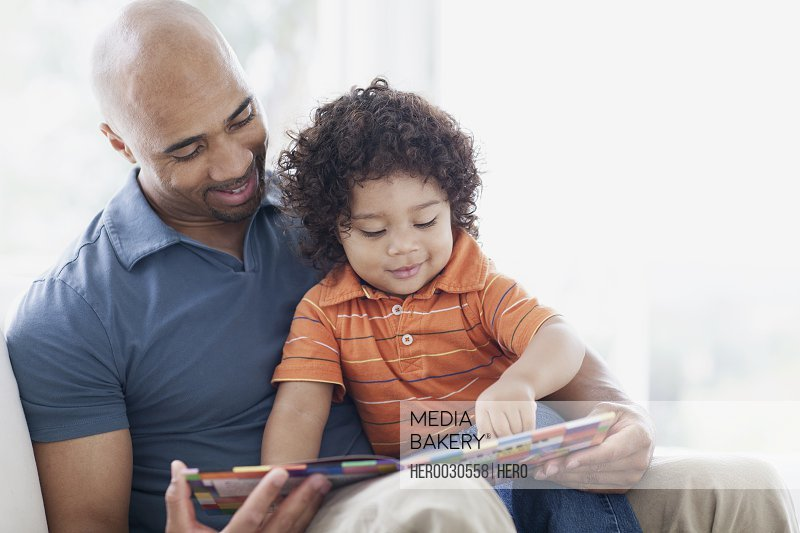 toddler sitting in fathers lap with book