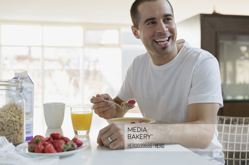 Man enjoying cereal and fruit for breakfast