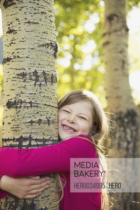 Cute girl with eyes closed hugging tree