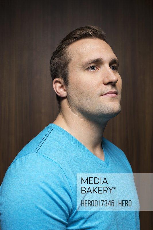 Serious man in blue t-shirt looking away