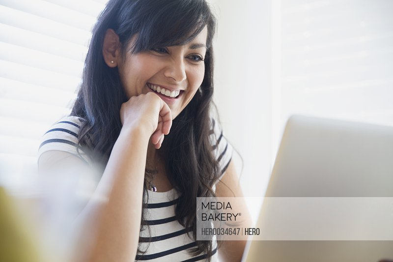 Happy mid adult woman using laptop at home