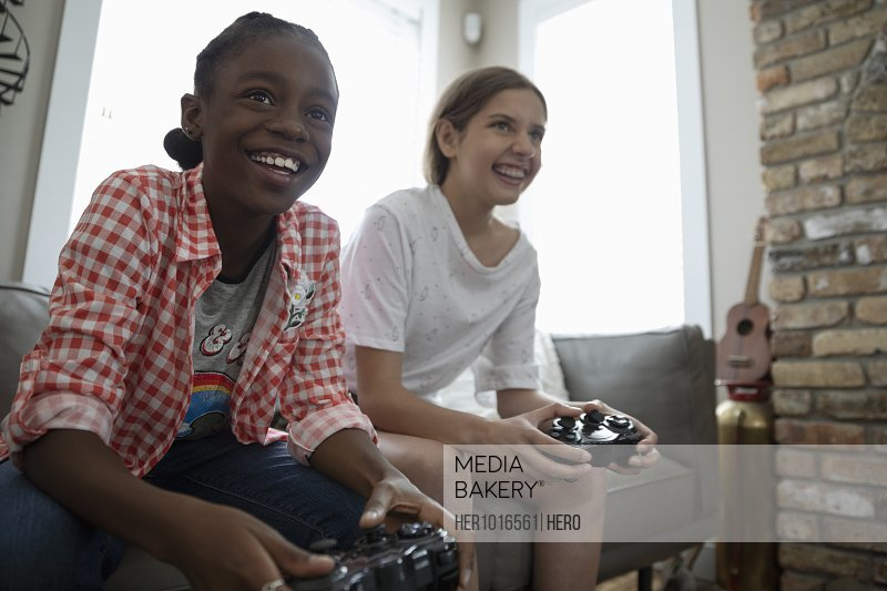 Smiling tween girl friends playing video game on living room sofa