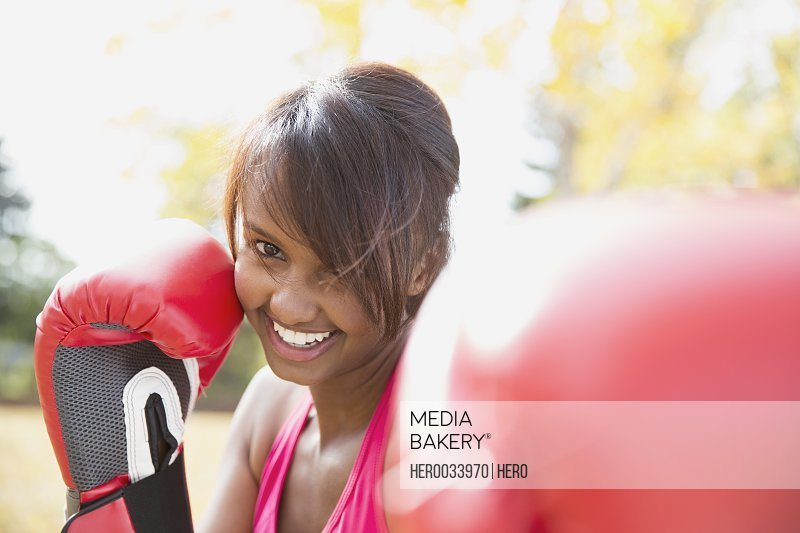 Woman with boxing gloves exercising outdoors.