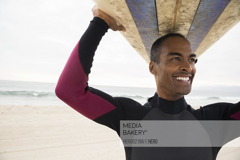 Smiling man in wetsuit holding surfboard overhead