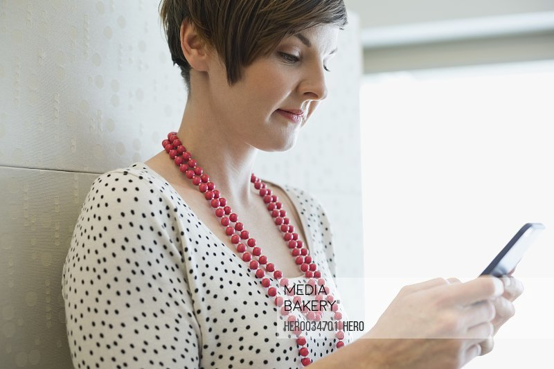 Side view of businesswoman text messaging