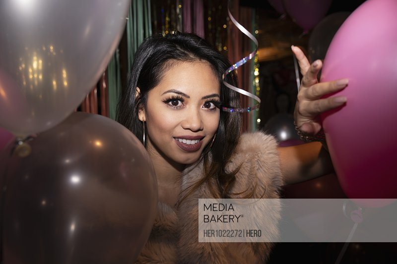 Portrait confident young woman with balloons at party