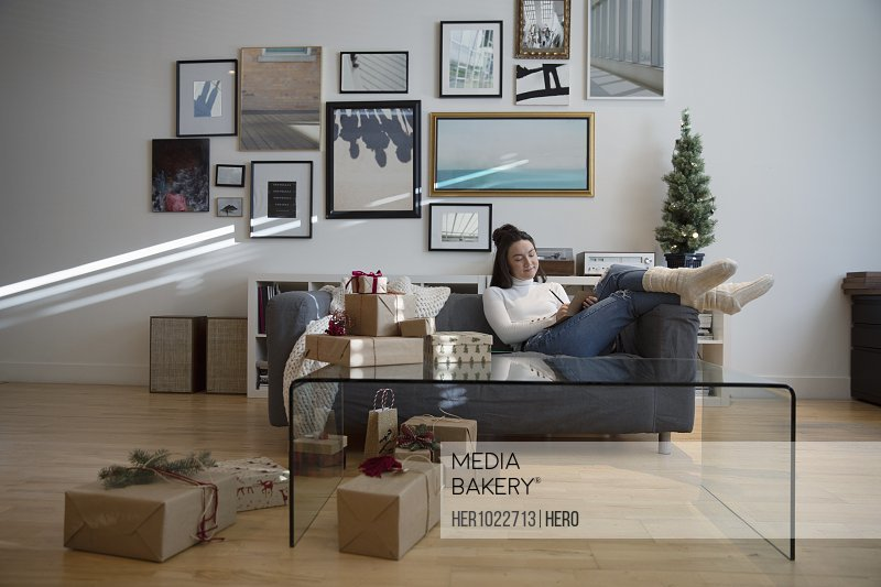Cozy young woman wrapping Christmas gifts in living room