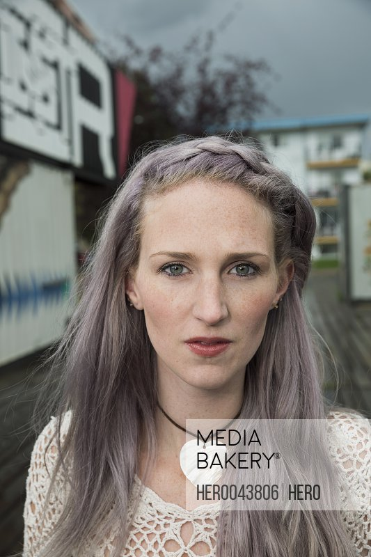 Portrait serious young woman with chalk dyed purple hair