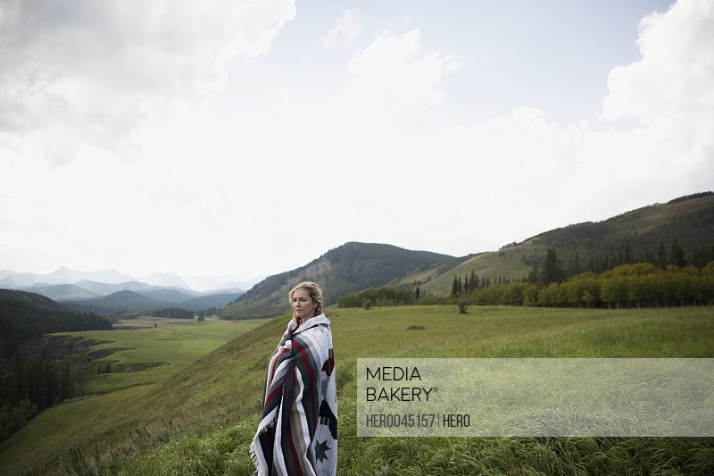 Woman wrapped in blanket in remote rural field