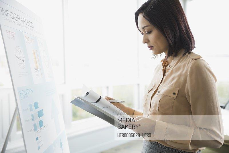 Businesswoman reading file in boardroom