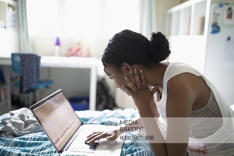 Teenage girl using laptop on bed