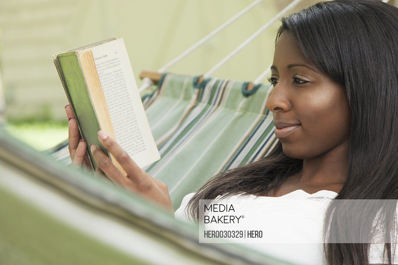 pretty african american woman reading book in hammock