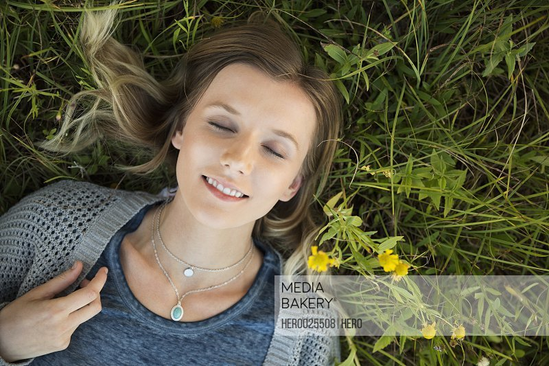 Overhead view serene young woman laying in grass
