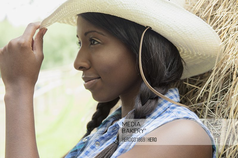 pretty african american woman tipping her straw hat
