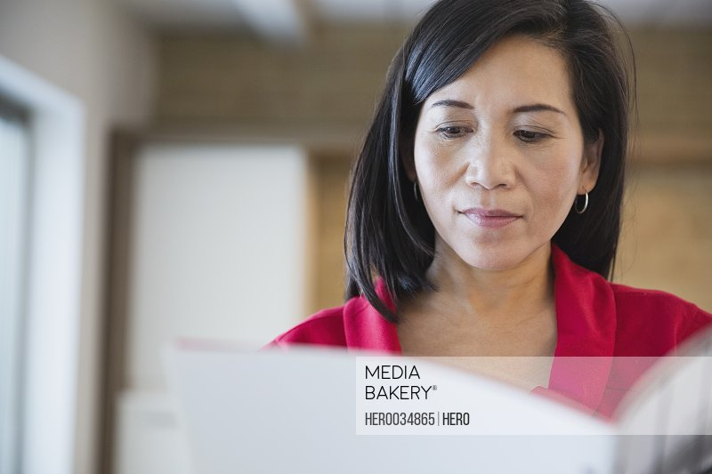 Mature businesswoman reading file in office