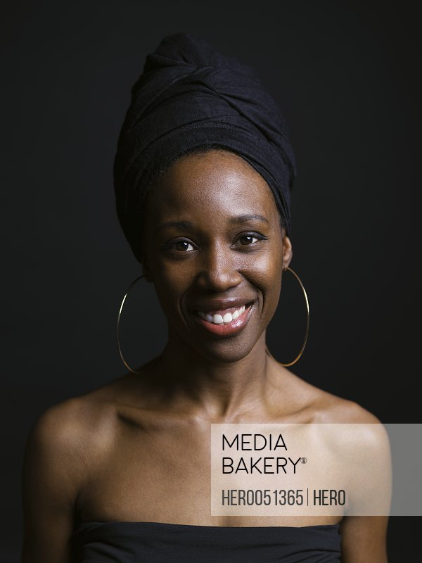 Portrait smiling African American woman wearing headscarf against black background