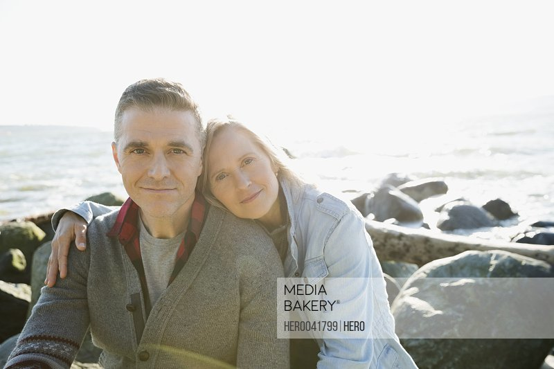 Portrait affectionate couple hugging on sunny beach rocks