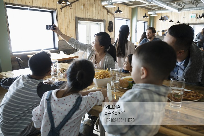 Family with camera phone taking selfie in restaurant