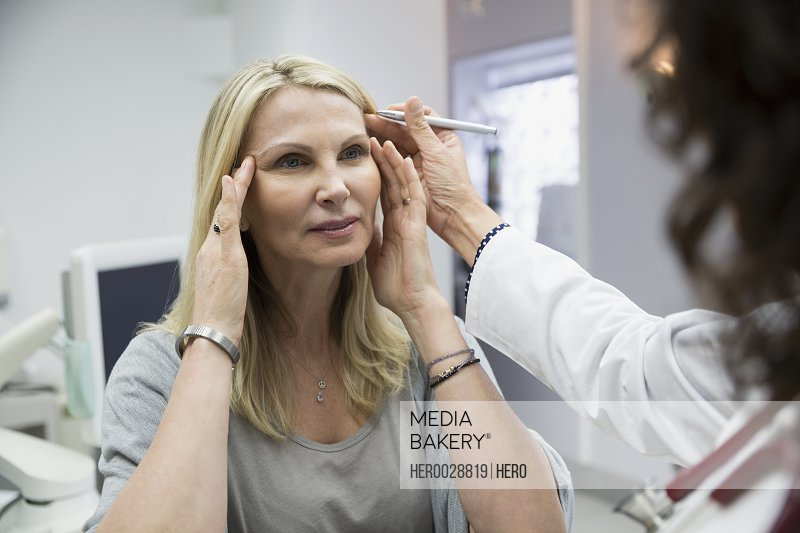 Plastic surgeon marking womans face in examination room