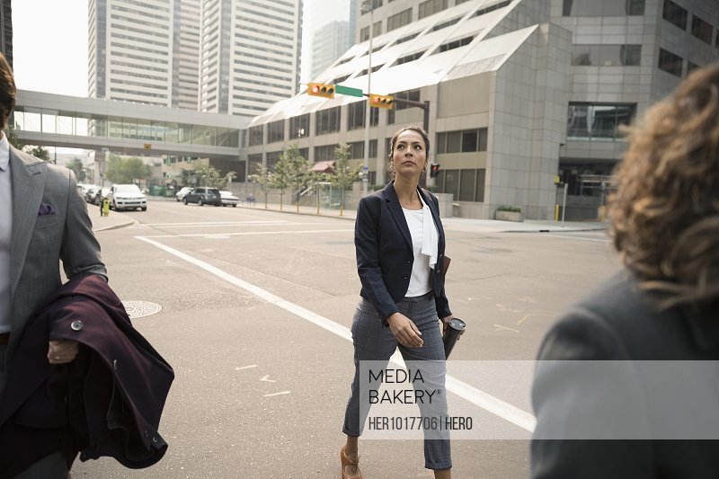 Businesswoman crossing city street