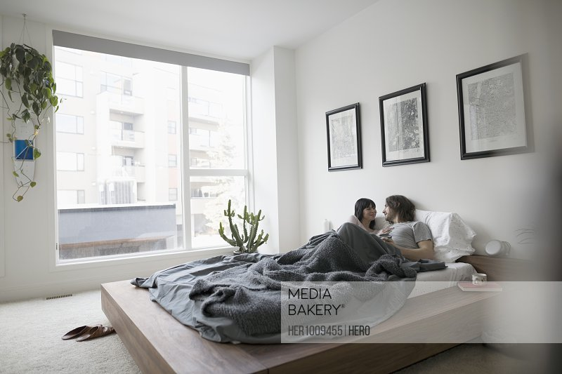 Affectionate couple cuddling in bed in urban apartment bedroom