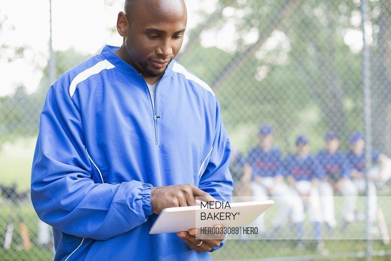 Baseball coach using pc tablet at ball game