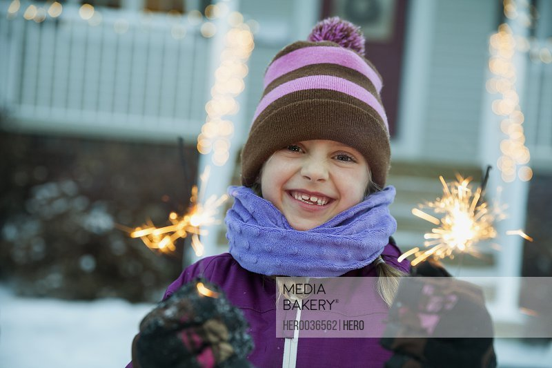 Girl holding sparklers outdoors