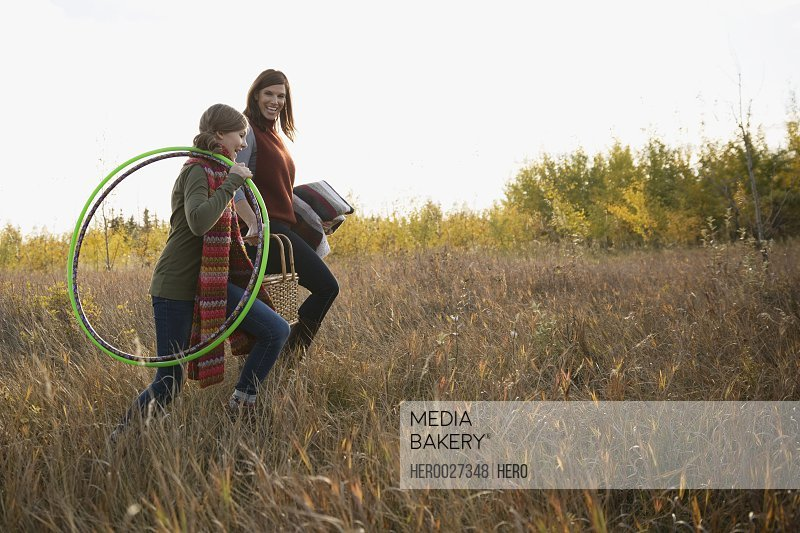 Mother and daughter carrying plastic hoops in field