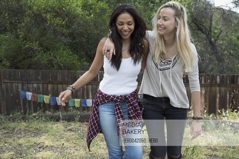 Smiling young women walking in backyard
