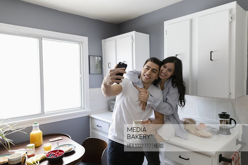 Happy young Latinx couple taking selfie in morning kitchen