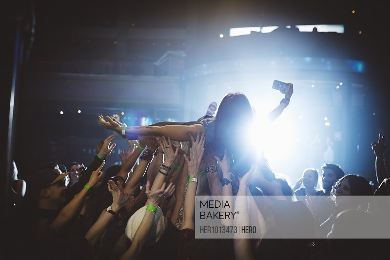 Woman with camera phone crowdsurfing at music concert in nightclub