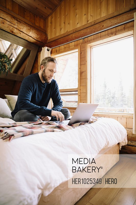Man using laptop on cabin bed