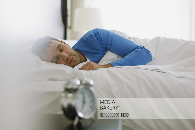 Man sleeping peacefully with alarm clock in foreground