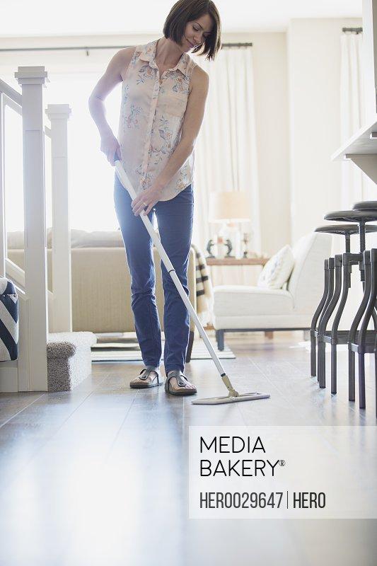 Mid-adult woman dusting modern wood floor