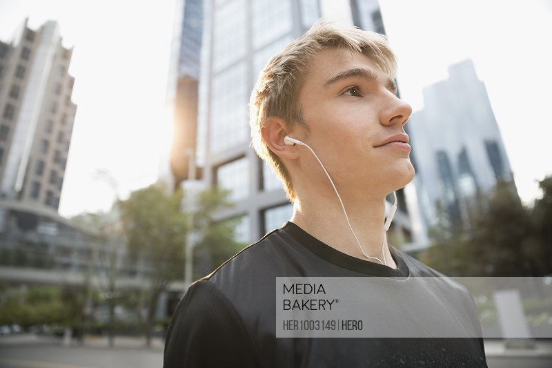 Serious young male runner listening to music on urban street