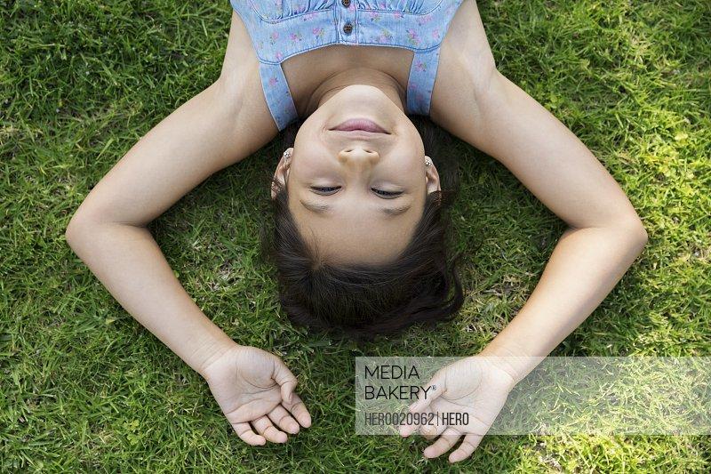 Overhead portrait brunette girl laying in grass