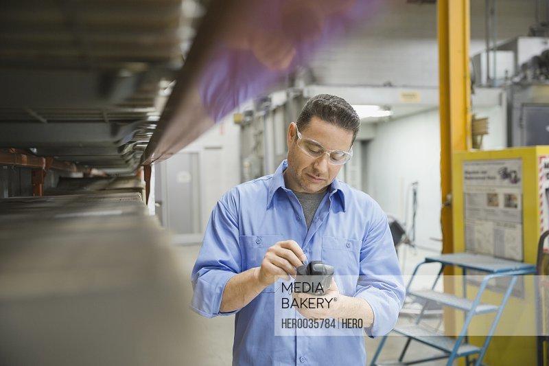 Worker using bar code reader in warehouse