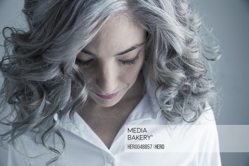 Portrait pensive Caucasian mid adult woman with curly gray hair looking down
