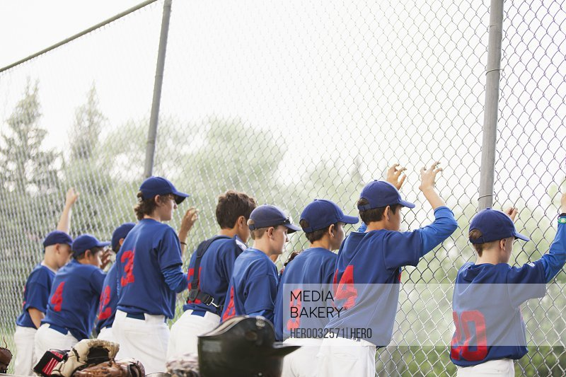 view from behind of boys baseball team along chainlink fence