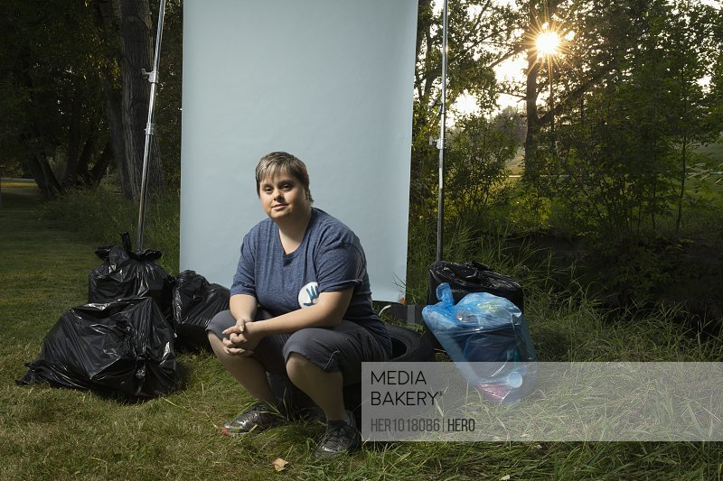 Portrait confident woman with down syndrome volunteering, cleaning up garbage in park, posing against white screen