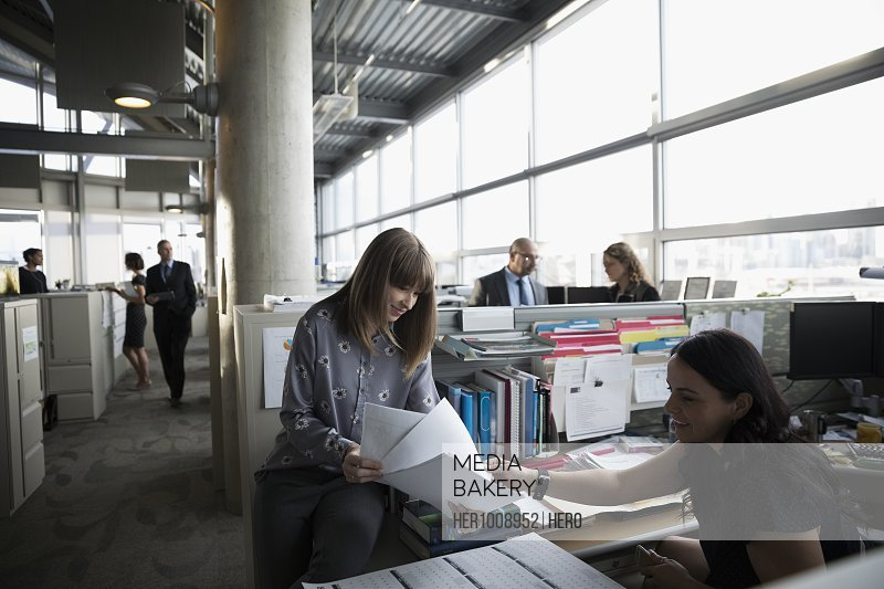 Businesswomen discussing paperwork at cubicle in open plan office