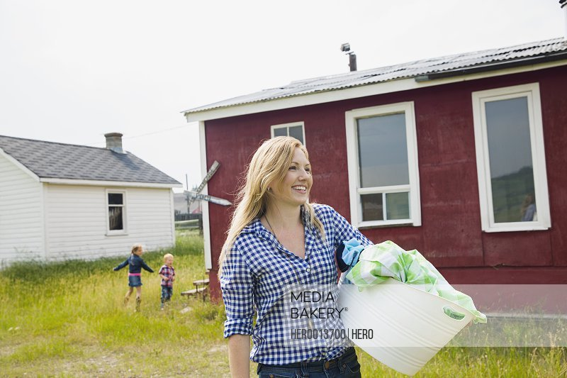 Smiling woman carrying laundry outside house