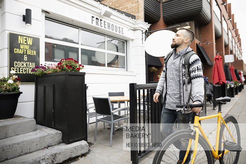 Man with bicycle outside bar