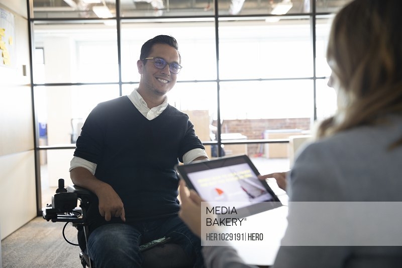 Businessman in wheelchair listening to colleague with tablet