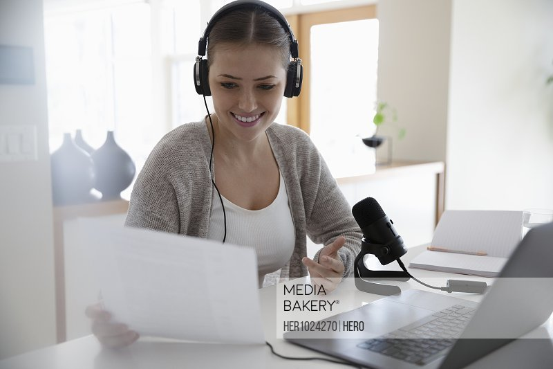 Smiling young woman with headphones and microphone vlogging at laptop