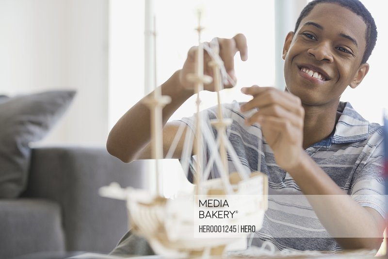 Teen building ship model at home