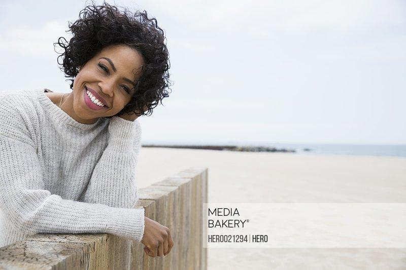 Portrait smiling woman curly black hair beach wall