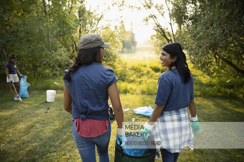 Mother and daughter volunteering, cleaning up garbage in park