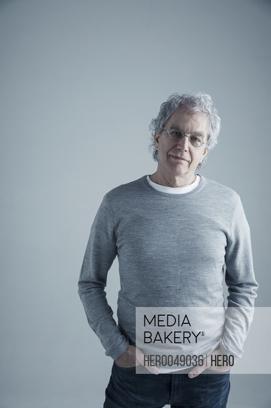 Portrait confident Caucasian senior man with gray hair and eyeglasses wearing sweater