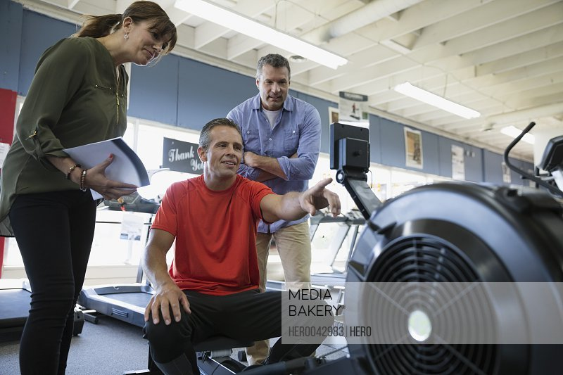 Salesman explaining rowing machine to couple in home gym equipment store